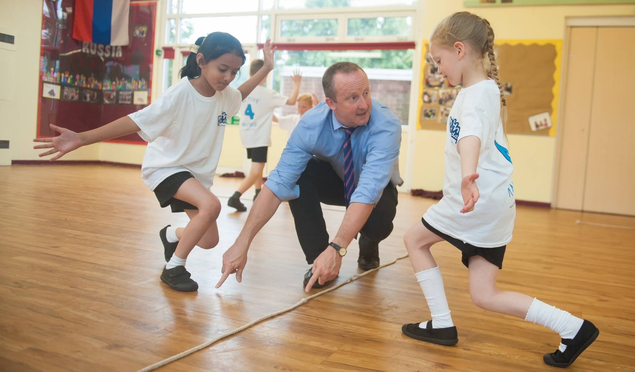 Children being taught a game with a skipping rope with Maths of the Day