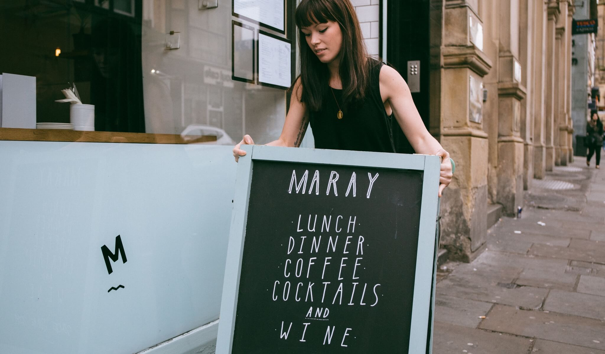 A sandwich board being placed outside Maray restaurant by a waitress